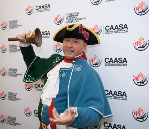 Man in colonial dress ringing a bell in front of a wall of CAASA logos